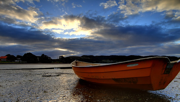 Boat on the beach just before sunset - Raglan, New Zealand