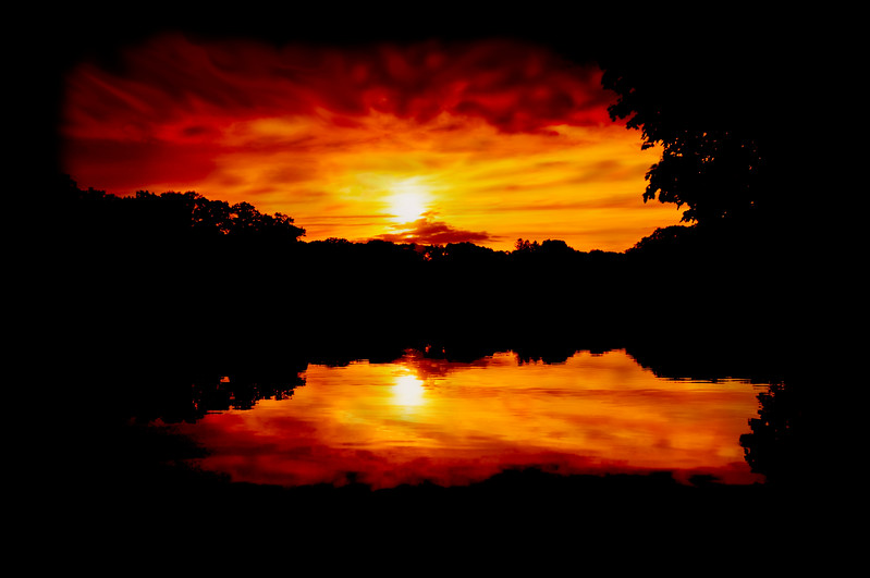"""<span style=""""color:red""""><center><em><h2><u>""""My FAVORITE SUNSET of ALL Time""""</u></h2></em></center></span> This Sunset came to me by accident / surprise really. I was set up around this lake taking reflection shots during the MAGIC LIGHT hour on a semi-cloudy day. When all of a sudden the sun popped out from behind the clouds and started heading for the horizon above the mountains.  """"SETTING UP THE SHOT"""" - I rushed to my bag and started setting up my Cokin """"P"""" filter system grabbing a 2 Stop Graduated Neutral Density filter first then stacked a Cokin Sunset Yellow filter in front of it then installed a Circular Polarizer on the lens to kill the glare off the lake. Prior to installing all the filters I took a meter reading exposing for the sky, added +1-2/3 Exposure Compensation to adjust up for the filters and then focused for the far tree line. You must take a meter reading and focus to set the shot up BEFORE the filters go on because with all the filtering the exposure in your view finder will be quite dark and you won't be able to properly see what your shooting at this point. I locked my D300 on a tri-pod and started cranking frames off using a cable release.  I couldn't believe the bold sky colors I was able to get using this filter set up and how well the bold black tree line silhouette set those colors off while still being able to capture the reflections of the clouds & sun in the lake with no glare and very little water ripple. Not more the 2 minutes later this scene was completely gone and darkness starting setting in. So it pays to be ready with your equipment for scenes like this, they come & go in the blink of an eye and being prepared for a sudden once of a life time shot is very gratifying to say the least. Had I missed this one I would have been one angry camper, but I was the victor this day and for that I'm very grateful.  ~Bill Pador~  * I hope you enjoyed this image as much as I did taking it, mother nature gave up one of her most beautiful gifts """