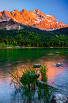 """""""Eibsee Sunset in the German Alps"""" Too often photographers are focused looking directly ahead at the big scene. This is one of those times when the scene BEHIND me was MUCH more exciting than a gigantic mountain right in front of me. While shooting sunset at the Eibsee Lake at the Zugspitze in the German Alps near Garmisch-Partenkirchen, the sunset behind me really started to come alive. I looked for the right composition and the curves of the lush green trees along the shore caught my eye. The subtle reflections in the water together with that symphonic feeling of the light concert above me. Wow.... what a feeling. Hopefully this captures some of that beauty to bring back to share. Lesson - Always turn around look around you! Even with a 10,000 foot mountain in front of you (which wasn't bad!), there might be other pictures around you. I'll keep this one. Let me know what YOU think!  — at Zugspitze."""