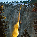 """Nature's Firefall"" is a rare photograph of Horsetail Falls in Yosemite at Sunset in winter. This is nature's version of the old man-made Yosemite Fire Fall.During the winter in Yosemite, coming off of El Capitan, there is an almost non-existent waterfall called ""Horsetail Falls."" Many maps don't even have it marked. During the last two weeks in February, IF there is water trickling over the edge, and IF it is clear at sunset (which doesn't happen too often due to the winter storms) the setting sun will turn this waterfall into a stream of molten fire. The waterfall lights up like molten lava due to the angle of the sun. Inspired by Galen Rowell, many photographers have chased this elusive photo opportunity. John spent two evenings in a foot of snow in the middle of meadow trying to get the shot. The first evening was an absolute bust as it had been clear all day and at sunset the clouds hung over the peak. Luckily he captured his photograph titled ""Full Moon over Half Dome"". The next evening everything worked out for this stunning shot.  I am debuting this week my latest images from my award winning trip to Yosemite.   <a href=""http://www.jharrisonphoto.com/gallery/7554507_MVWMR""target=""_blank"">My Yosemite can be seen here.</a>   Let me know which ones you like!  Thanks, John"