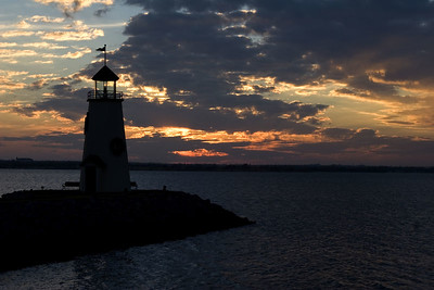 Stock photo of a sunset on the lake with a lighthouse in the foreground.