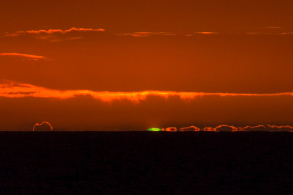 "Green flash. This is a mirage that occurs when sunlight passes through earths atmosphere. For a more detailed explaination go here:  <a href=""http://www.exo.net/~pauld/physics/atmospheric_optics/green_flash.html"">http://www.exo.net/~pauld/physics/atmospheric_optics/green_flash.html</a>"