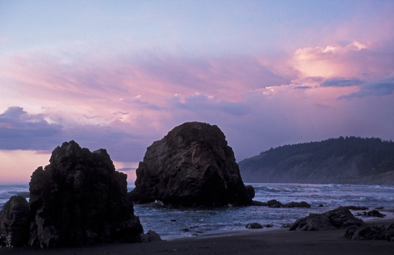 Large rocks off the beach under pink storm clouds at sunset.  Mendocino county, California.