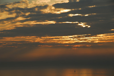 A lone sailboat at sunset off the coast of Genoa, Italy.