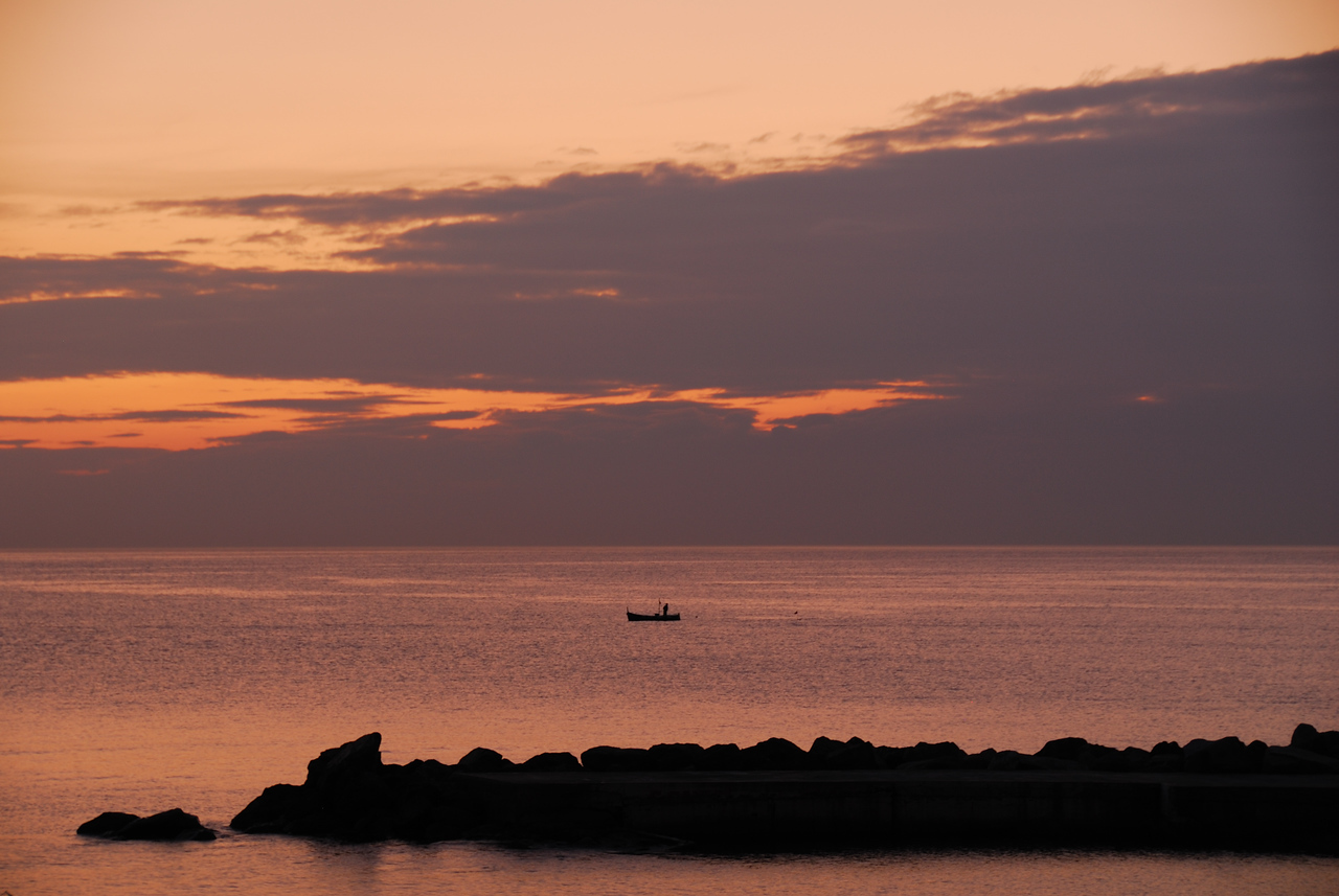 A fisherman retrieves his nets at sunset off the town of Camogli, Italy