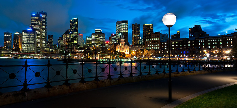 Sydney Skyline at Night. I captured this a few months ago and just reprocessed this. I love night skylines especially when you get the water reflections of the color of the lights. I did one crop without the lamp post and buildings to the right of it, but it wasn't as interesting imho - I like the path that takes you walking along together with the subtle wrought iron fence. For the technical details -- This is about 10 images shot vertically with my Nikon f/2.8 28-70 (love that lens!). 10s at f/16. Stitched together in Photoshop CS4. Post in LR and PS. The amount of detail in the image is stunning when you look at the high res!