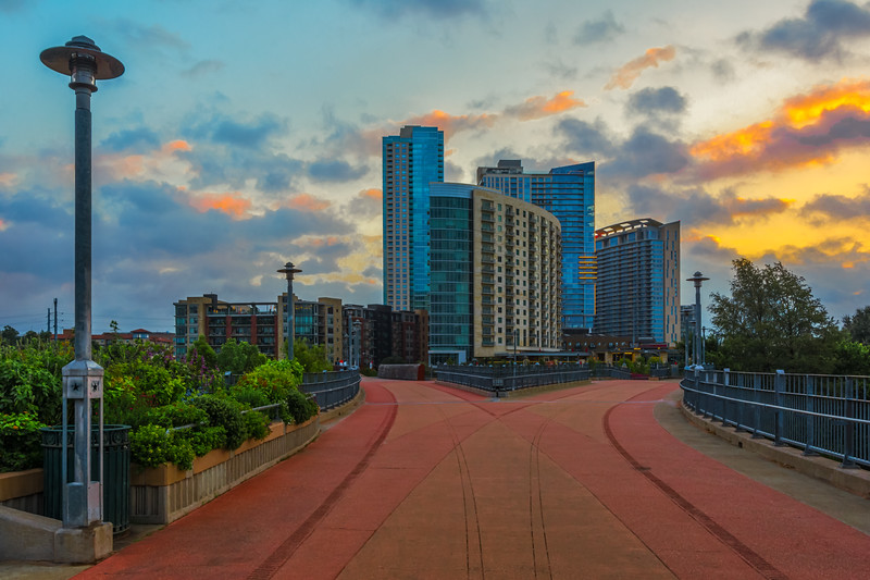 Photo of the Pfluger Pedestrian bridge with the Gables Park Tower apartments at sunrise.