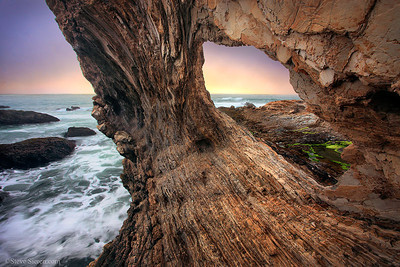 Hidden sea arch along the California Central Coast frames a pacific sunset.