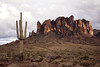 "The Superstition Mountains / Lost Dutchman Legend<br /> <br /> The Superstition Mountains (their name inspired by Pima Indian legends) have been a source of mystery and legend since early times. The area is dotted with ancient cliff dwellings and caves, many showing signs of former habitation. It is not certain who these people were; some believe they were Salado or Hohokam Indians who populated this part of Arizona several centuries ago. Later, Pimas and ""Apaches"" (some of whom may have been Yavapais) occupied parts of the region. However, the name ""Apache"" came to be closely associated with the Superstitions, and the mountains became an Apache stronghold in the 1800s.<br /> <br /> During the 1840s the Peralta family of northern Mexico supposedly developed rich gold mine(s) in the Superstitions. Their last expedition to carry gold back to Mexico occurred in 1848. According to legend, the large party was ambushed by Apaches, and all were killed except for one or two Peralta family members who escaped into Mexico. This area is known today as the Massacre Grounds.<br /> <br /> A number of other people were supposed to have known the mine's location or even to have worked it. Numerous maps have surfaced over the years, only to become lost or misplaced when interested parties pressed for facts. Men who claimed to have found the Peralta mine were unable to return to it or some disaster occurred before they could file a claim, all adding to the lore of a ""lost mine.""<br /> <br /> In the 1870s Jacob Waltz, ""the Dutchman"" (actually a native of Germany) was said to have located the mine through the aid of a Peralta descendant. Waltz and his partner, Jacob Weiser worked the mine and allegedly hid one or more caches of gold in the Superstitions. Most stories place the gold in the vicinity of Weaver's Needle, a well known landmark. Weiser was killed by Apaches, or according to some, by Waltz himself.<br /> <br /> In failing health, Jacob Waltz moved to Phoenix and died some twenty years later in 1891. He supposedly described the mine's location to Julia Thomas, a neighbor who took care of him prior to his death. Neither she nor dozens of other seekers in the years that followed were able to find the ""Lost Dutchman's Mine."" Subsequent searchers have sometimes met with foul play or even death, contributing to the superstition and legend that surround these mountains.<br /> <br /> Many versions of the ""Lost Dutchman Mine"" story exist, and several books and films have been done on the subject."