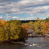 The view from a disused train tressle bridge over the Merrimack in Manchester, NH.  The sun lit up the near trees, but the far horizon is still in shade.