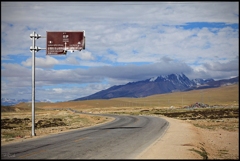 Road sign with Mount Nyenchen Tanglha at the backdrop