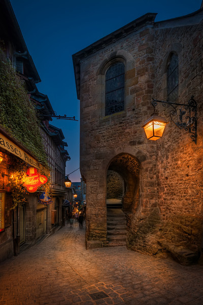 At daytime Mont Saint Michel is crowded with tourists, but later, when the sun is down people leave the place. It's a labyrinth of small streets and alleys criss crossing their way to the entrance of the monastery on the top of the mountain. Small lamps light up and make it very Harry Potter medieval town. Photo by: Jacob Surland, www.caughtinpixels.com