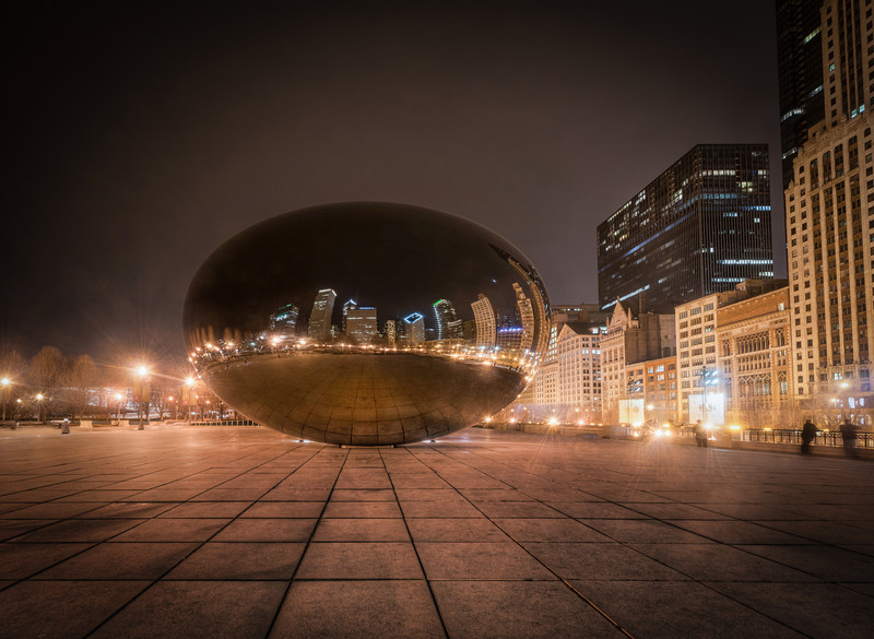 Bean at Night The Bean in Chicago is an awesome pieace of art. Though I only had very little time in Chicago I managed to get by it three times, the last time was at night time. The bean is a huge mirror built in steel, and then shaped like a bean. Everything reflects in the bean but in strange ways, because of the curves. It's very fascinating.