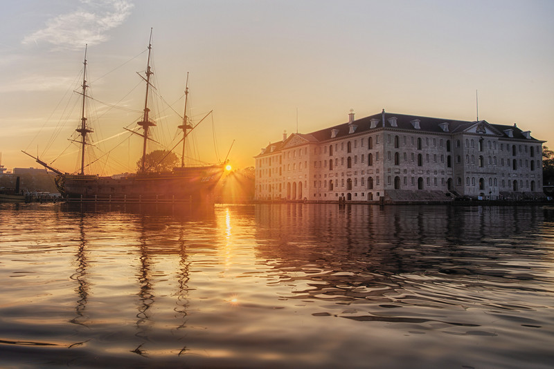 Amsterdam Maritime Museum and the old 3 mast sail ship seen just in the sunrise. Shot from a low point of view to capture the beauty of the calm water. More photos by Jacob Surland on www.caughtinpixels.com. Here you can find tutorials too.