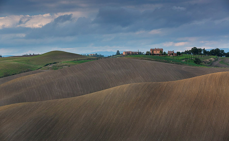 The perfect smooth curves of Tuscany rolling hills touched by the last ray of sun light.