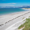 From the dunes atop Berneray West beach looking north along a seaweed high tide mark to the mountains of Harris. <br /> Crowded beach isn't it!