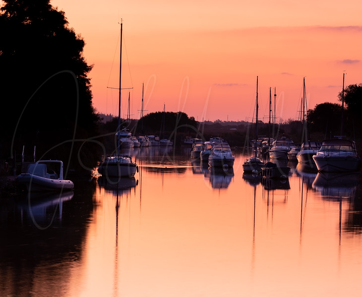 Boats moored in the River Frome during Golden Hour