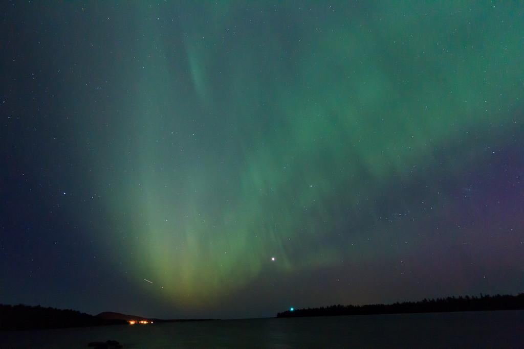 Aurora Borealis over Copper Harbor. Lighthouse is green light in center. Copper Harbor lower left.