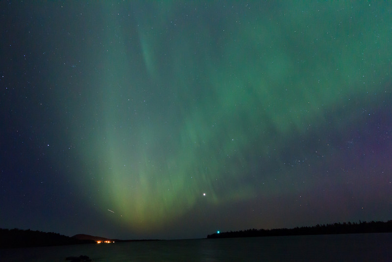 Aurora Borealis over Copper Harbor. Lighthouse is green light in center. Copper Harbor lower left.