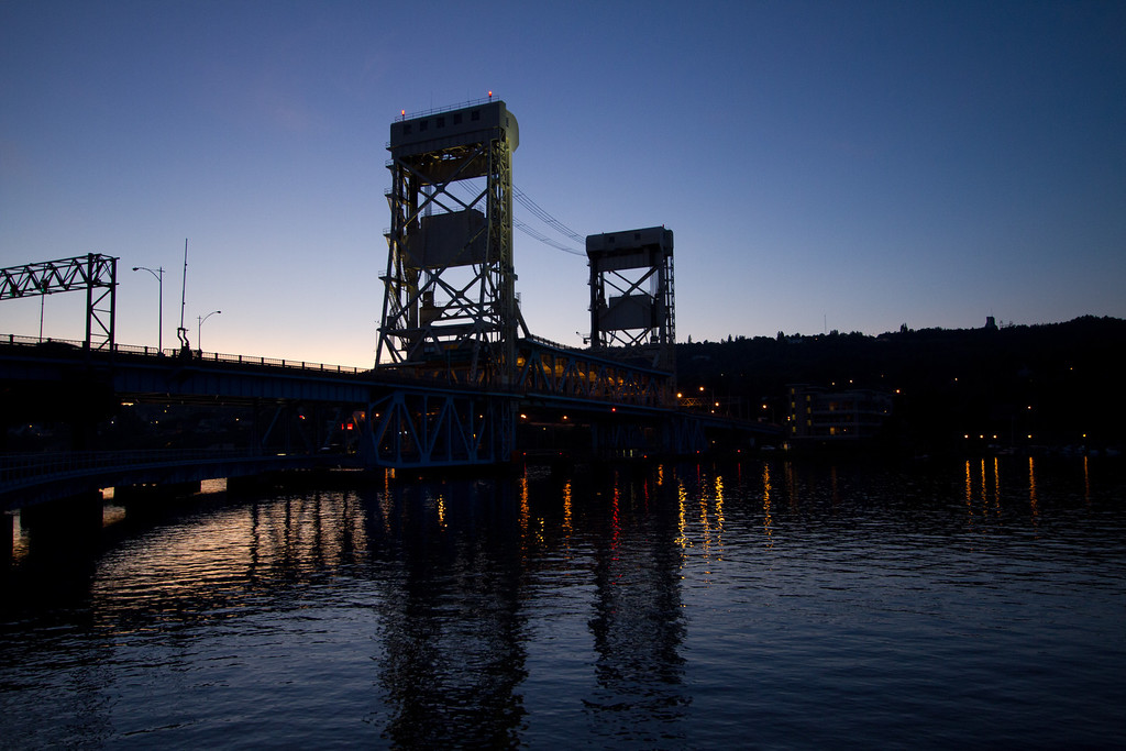 The lights of the Portage Lift Bridge begin to illuminate the water at dusk.