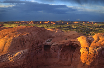 Sunlight from a clearing storm bathes 2 pothole arches and distant rock formations in rich, beautiful color. This scene is opposite Delicate Arch as viewed from the main Delicate Arch viewpoint at the end of the hiking trail.