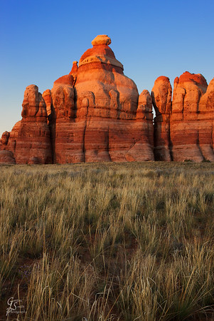 Chesler Park Monuments at Sunset With grass in the meadows and last rays of sun shining on the upper half of this sandstone monument.