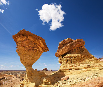 Weird World with slanted hoodoos and puff-dot clouds leaning towards the central distant sandstone tower