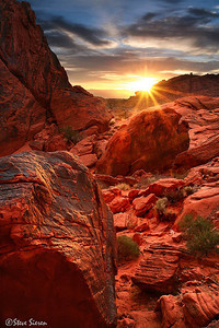 Melting the Shadows Valley of Fire State Park, Nevada  After visiting Valley of Fire State Park over the years and looking back at this image it really speaks of the name of the place. The back light illuminating all of the red rock as the warmth melts away the cold shadows from the previous night. It's shot from with in the Valley of Fire, one of the canyons looking off into the sunrise across the valley floor. Most photographers think of Utah when it comes to red rocks but it's heavily found in part of Nevada as well.