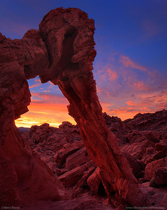 Fiery sunset through Elephant Rock Arch at Valley of Fire State Park in Nevada's Mojave Desert.  This is two merged images with a tilt shift lens to add a little more mega pixels to file and get the 4x5 format instead of the normal 4x6 format created from DSLR cameras. It's a great technique to have available but it's only used every now and then. I prefer zoom lenses when I'm shooting but primes are always a little sharper.