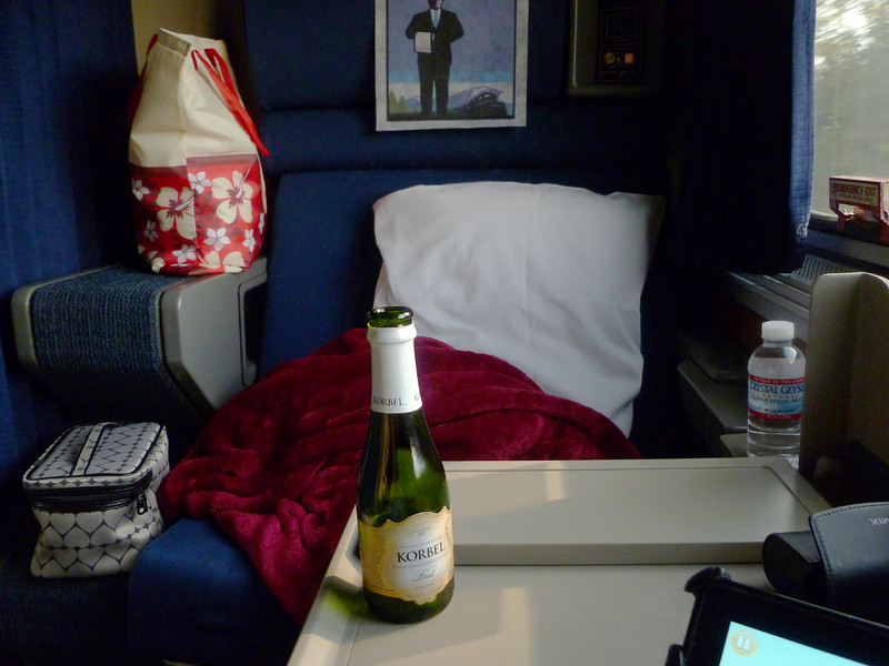 My roomette on the Starliner--the attendant offers you champagne when you first board. You could have sparkling cider instead if you like. Overhead, there's a bunkbed that folds down, and these lower chairs also fold down into a bed. The window stretches the length of the room.