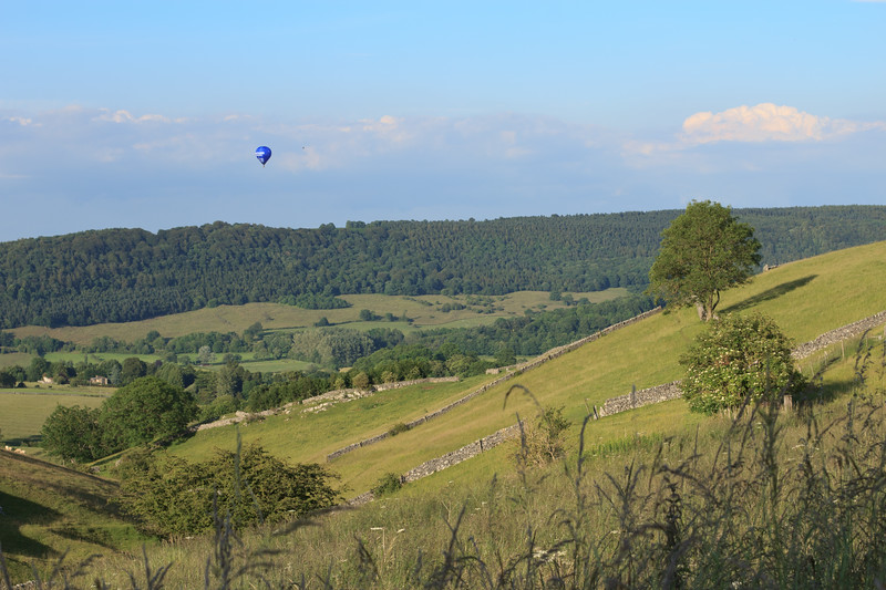 A hot air balloon sails over Ditch Cliff, near Bakewell in Derbyshire.