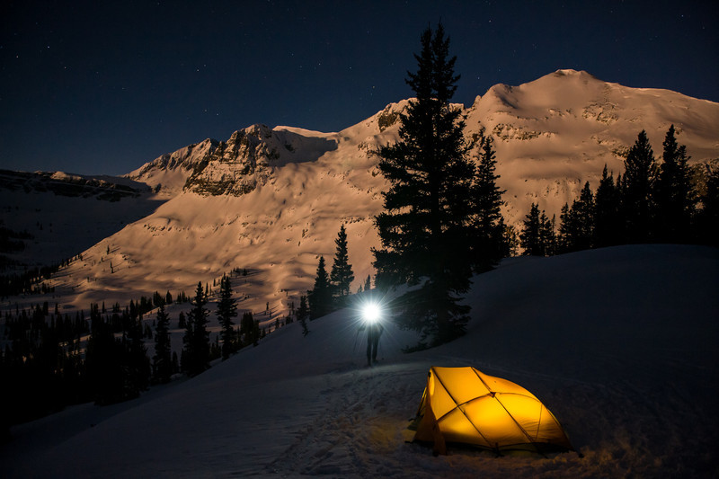The moon rises behind a winter campsite.