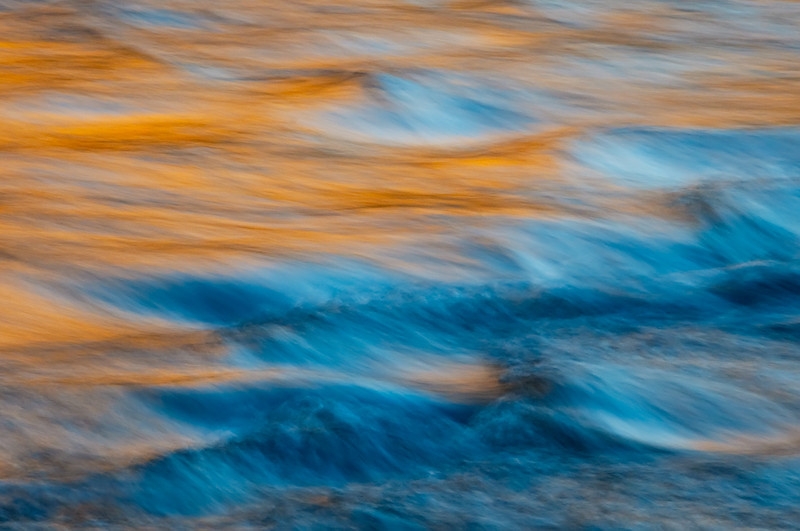 """Sunset Flowing"", Yosemite National Park, Aperture Nature Photography Workshop Contest trip.  ""Water, Light and Textures"" series.    We were shooting at Valley View at sunset with stark blue skies.  Scott Bourne had been reminding us to look around and find the smaller images - don't always look for the big picture that anyone else can shoot.  The reflected orange glow from El Capitan just lit up the Merced and I found this soothing image.   This image is inspired by Charlie Cramer and Michael Frye. This image is available as a canvas giclée gallery wrap in sizes 16""x24"", 20""x30"", 28""x42"" and 38""x58"""