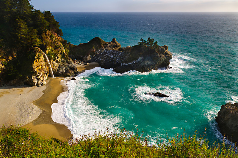 """McWay Falls, Julia Pfeiffer Burns State Park""  McWay Falls is one of those hidden California treasures located thirty minutes south of Big Sur in Julia Pfeiffer Burns State Park.  This waterfall spills right into the ocean surrounded by this private secluded beach. The bright green water and white sands has many people think this is an image from Hawaii!   That beach makes you want to just get your chair, drinks and take out from Mike's Cafe and sit right down by the waterfall.  Another great place to be on a Friday afternoon."