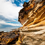 "12/4  ""Rock Layers to the Sky""  Royal National Park, 1 hour South of Sydney near Bundeena.  This was earlier in the afternoon at the coast at the Royal National Park.  Just God's playground of rock textures, shapes and patterns. Add a rich blue and cloudy sky, mix in an ultra-wide angle lens that I love to use and you have a rockin' combination!"