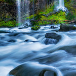 """""""Waterfalls flowing from Moss""""  The water was just flowing out of the moss and into the river. This tranquil and peaceful scene has those combinations of angles, lighting in the backdrop, smooth water and streams of water coming out of the lush green moss.  That perfect setting to bring you back to nature."""