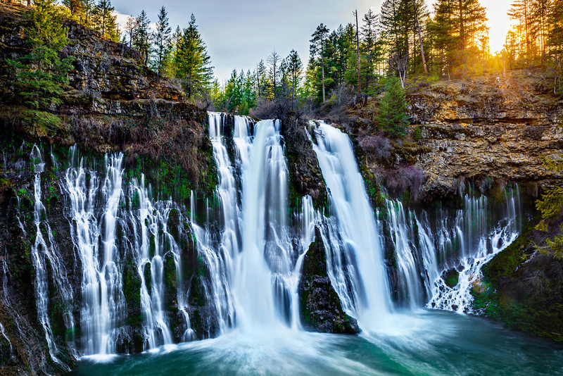 """Burney Falls at Sunset"" Burney Falls State Park has been on my list of awesome waterfalls to visit for a while! I had the chance to go at the last minute and we caught it just as the sun was setting! Quite the roar from the falls. It is a spring fed falls moving over 100 million gallons per day!! It was hard to get a sense of just how large it is at 129 feet tall and twice as wide. In the summer it must be quite the swimming hole! Burney Falls State Park is about an hour East of Mt Shasta and should be added to the California must see list! More info is here on the state park website. Enjoy! <a href=""http://www.parks.ca.gov/?page_id=455"">http://www.parks.ca.gov/?page_id=455</a> Copyright John Harrison Photography"
