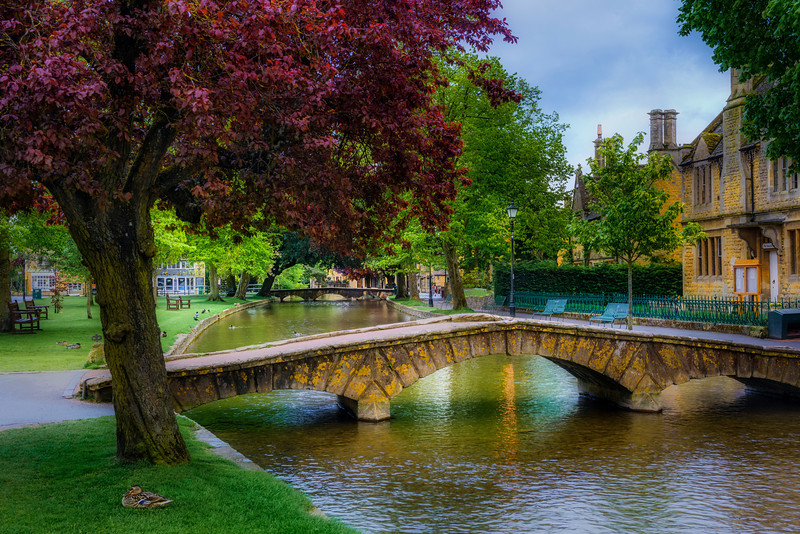 """""""Scenes in Bourton-on-the-Water"""" Bourton-on-the-Water is a village in Gloucestershire, England that is one of my favorites! I visited this summer and stayed right in the village. This scene feels just like a Thomas Kinkade painting with ...See More<br /> — in Bourton on the Water, United Kingdom.   Gloucestershire, near Oxfordshire, Oxford, Cotswolds, England, United Kingdom"""