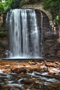 Looking Glass Falls, near Brevard, NC. Brevard, in Transylvania county easily contains more significant waterfalls than any other county in NC and more than most counties in the nation. Transylvania County is said to have more than 500 major  waterfalls. Looking Glass gets its name from fact that when sunlight shines on falls, it appears like a mirror. In addition, you can walk behind falls and peek out from the back side. It was very difficult to get picture, without folks in photo. This photo required a tripod and self in the water. 5/21/2011