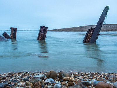 The tide flows out through what is left of the breakwater