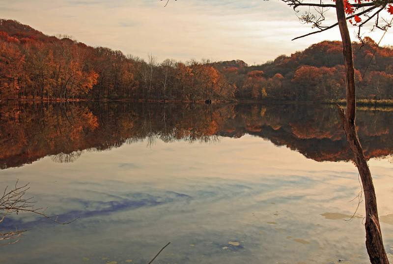 A perfectly smooth Radnor Lake reflects the autumn sky.