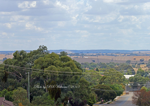 An elevated view from Boorowa township looking west. The dust at centre of screen is being stirred up by graders strengthening containment lines around the fire on Sunday 20th January 2013.