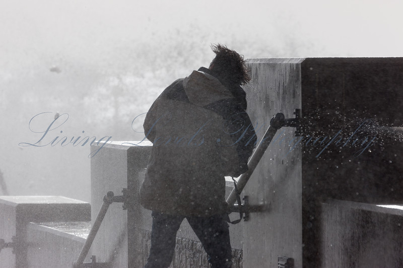 As waves break over the sea wall at West Bay a photographer gets a soaking