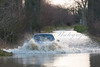 Car getting swamped as it tries to drive through the flood on Street Drove in the Somerset Levels between Glastonbury and Street