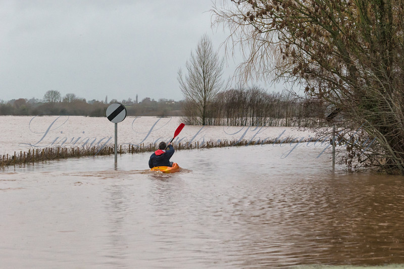 Canoeist paddling down flooded Cuts Rd, Burrowbridge after the River Tone burst its banks in the recent floods