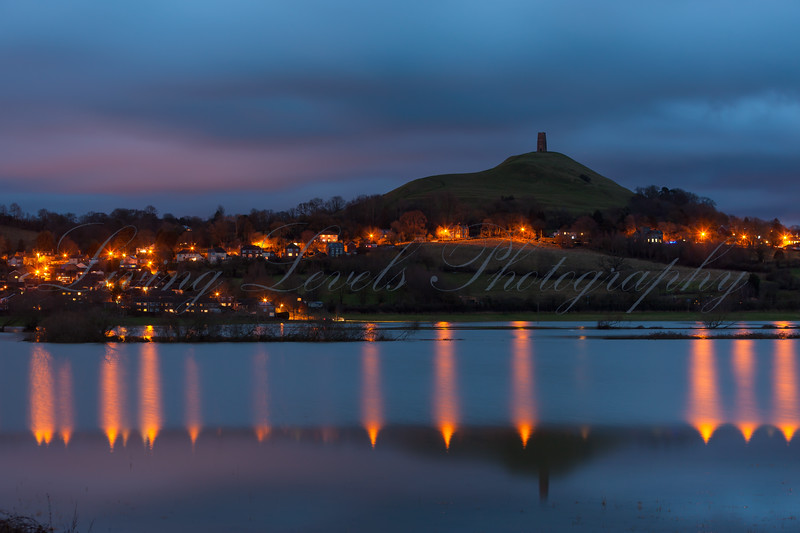 Glastonbury Tor taken from the South, reflected in flood water at twilight.