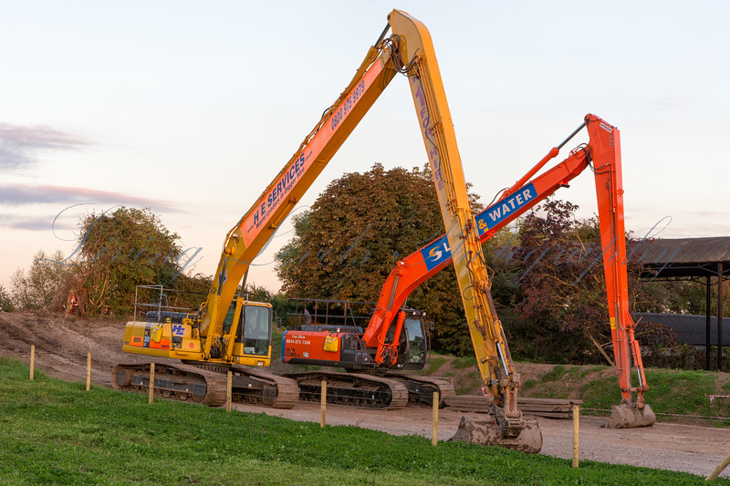 Long-reach excavators parked up at the end of another busy day dredging the main channel of the River Parrett  at Burrowbridge