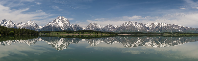 The Tetons reflected in Jackson Lake. The Tetons rise abruptly from an elevation of 6,770 feet at the lake; the highest peak - Grand Teton- is at 13,776 feet.