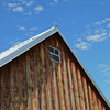 Roof top of old barn against a blue sky