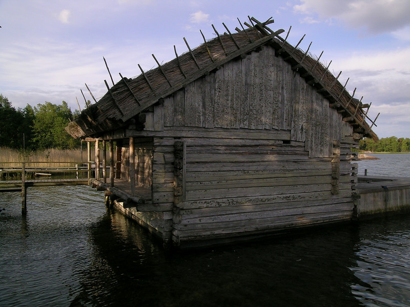Old boat house with roof made from marsh reeds seen growing in the background.  Åland Islands, Finland.